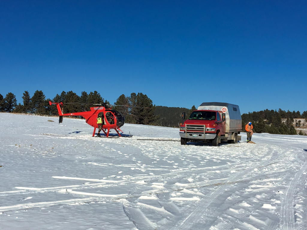 A crew refuels and restocks the Hughes 369D helicopter. Researchers on the helicopter caught elk and fitted them with tracking collars Friday. Photo Date: Dec. 7, 2018.