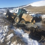 Equipment submerged in mud after snow melt and flooding on Pine Ridge