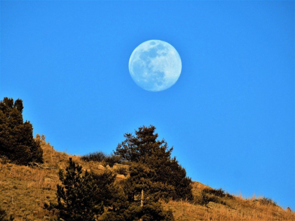 Moon during the day over the hills