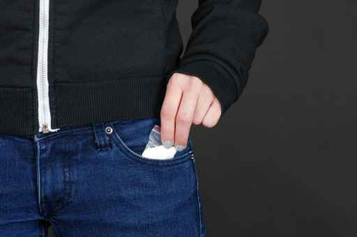 teenager pulls drugs out of jeans pocket