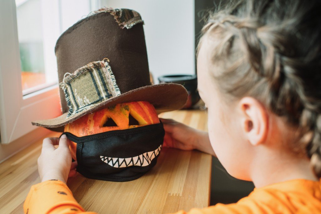 Child Putting Protective Mask On Jack O'lantern For Halloween