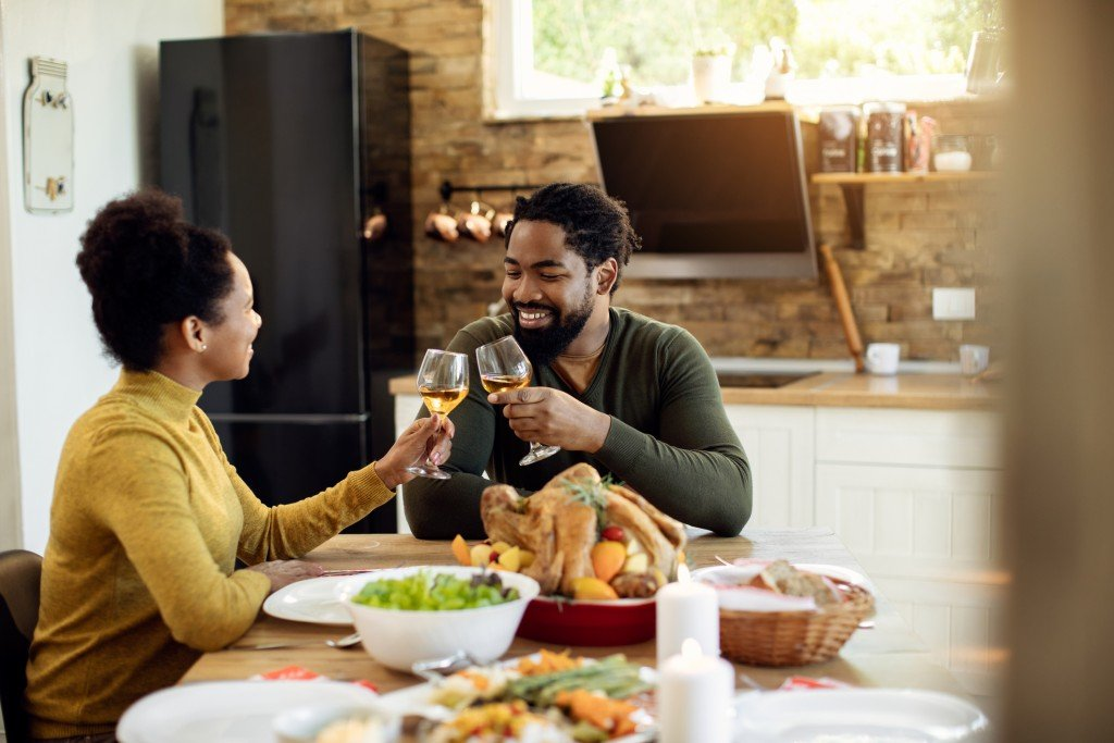 Happy African American Couple Toasting During Thanksgiving Meal In Dining Room.
