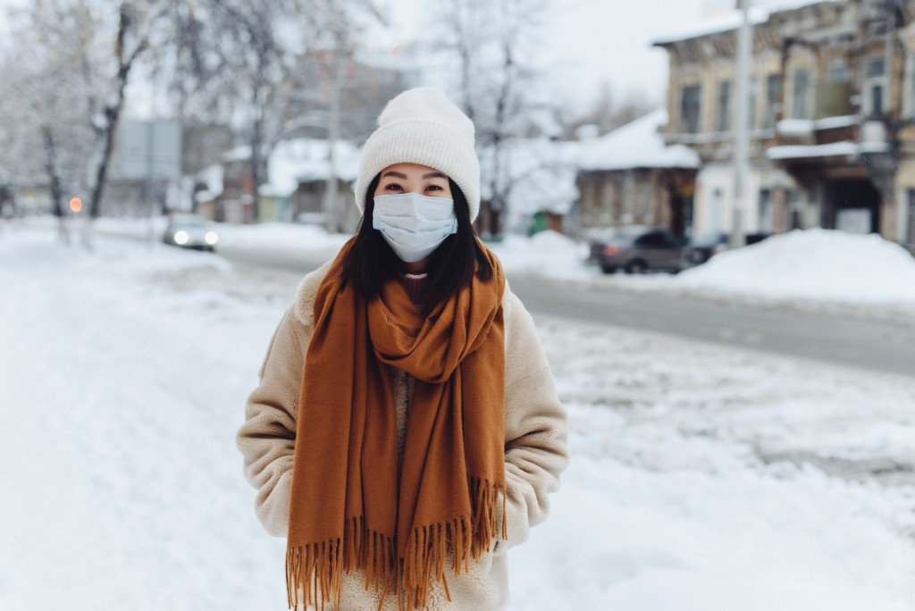 Passerby Asian Girl In A Protective Medical Mask Outdoors. A Woman On The Street In Winter Protects The Respiratory Tract From The Epidemic Of Coronavirus. Protection Against Urban Smog And Dust
