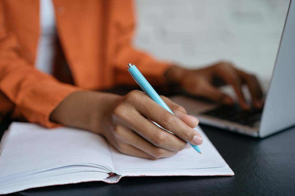 Close Up Shot Of Student Hand Holding Pen And Writing In Notebook, Working At Home. E Learning