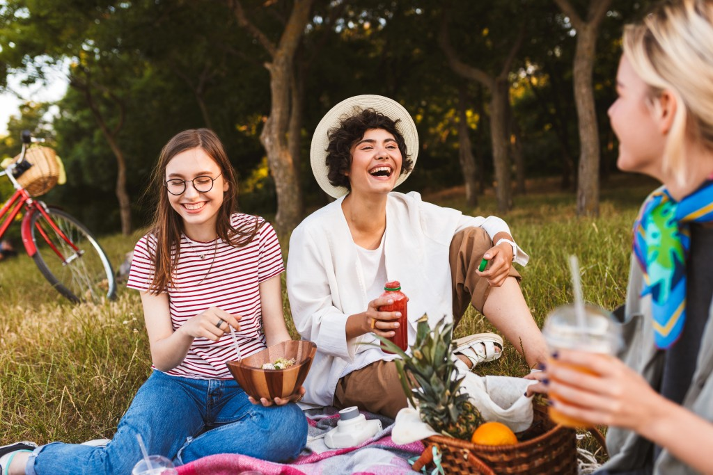Smiling Girls Sitting On Picnic Blanket Joyfully Laughing Spendi