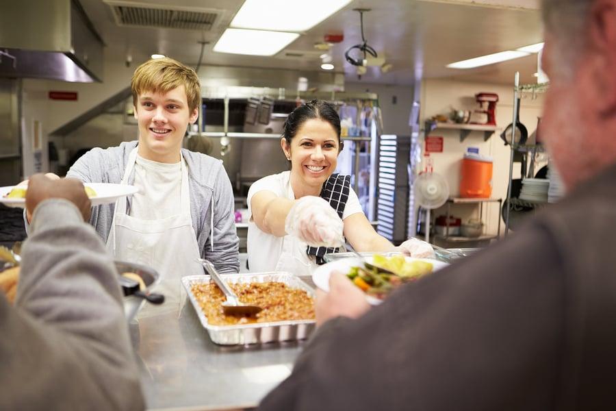 Bigstock Staff Serving Food In Homeless 62500892
